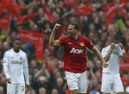 Manchester United's Rio Ferdinand celebrates his game-winning goal against Swansea City during the English Premier League soccer match at Old Trafford stadium in Manchester