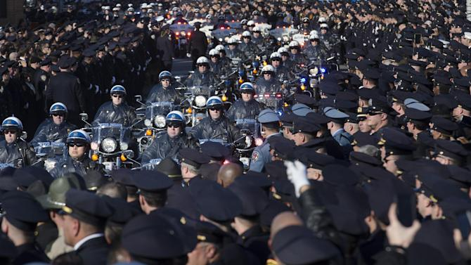 Motorcycle officers lead the funeral procession of New York city police officer Rafael Ramos in the Glendale section of Queens, Saturday, Dec. 27, 2014, in New York. Ramos and his partner, officer Wenjian Liu, were killed Dec. 20 as they sat in their patrol car on a Brooklyn street. The shooter, Ismaaiyl Brinsley, later killed himself. (AP Photo/John Minchillo)