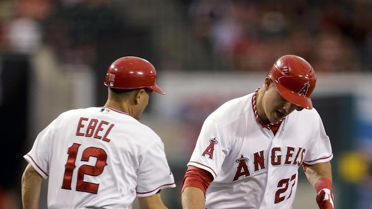 Los Angeles Angels' Mike Trout, right, celebrates his home run with third base coach Dino Ebel during first inning of an baseball against the Boston Red Sox in Anaheim, Calif., Tuesday, Aug. 28, 2012. (AP Photo/Chris Carlson)