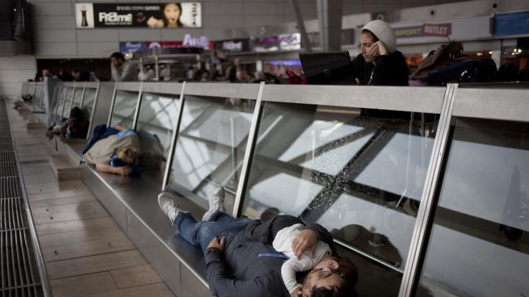 "Passengers wait in a departure hall at the Ben Gurion airport near Tel Aviv, Israel, Sunday, April 21, 2013. Israel's three airlines went on strike Sunday over a proposed ""Open Skies"" deal with the European Union that union workers say jeopardizes their jobs and could even cause the local airline industry to collapse. (AP Photo/Ariel Schalit)"