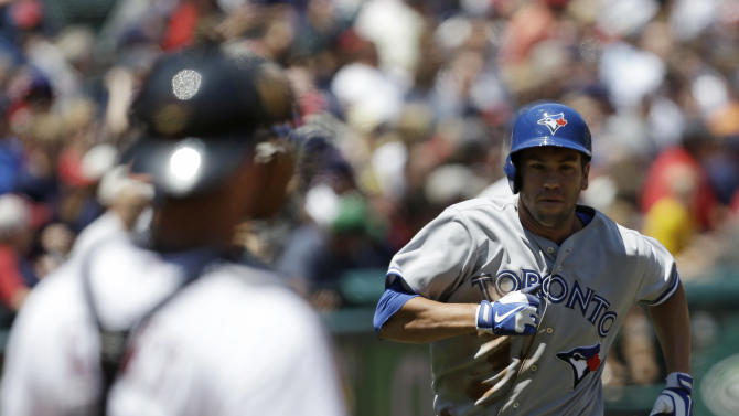 Toronto Blue Jays catcher Josh Thole, right, scores on a double by Jose Bautista in the sixth inning of a baseball game against the Cleveland Indians, Thursday, July 11, 2013, in Cleveland. (AP Photo/Tony Dejak)