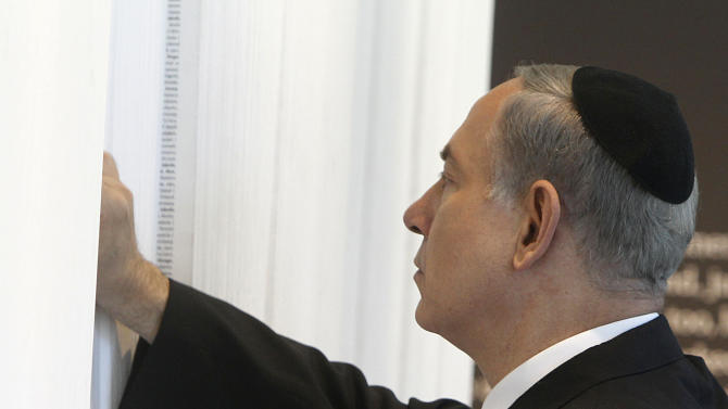 "Israeli Prime Minister Benjamin Netanyahu looks at ""The Book of Names"", which contains the names of 4.2 million Jews killed during the Holocaust, at the opening of a new pavilion at the former Nazi German death camp of Auschwitz, in Oswiecim, Poland, Thursday, June 13, 2013. The exhibition in Bloc 27 was curated by Israel's Yad Vashem Institute Chairman Avner Shalev. It is meant to educate visitors about the Holocaust and the Nazi Germany's quest to exterminate the Jewish people. The event closed Netanyahu's two-day visit to Poland that was steeped in symbolism, as it focused on the Jewish people's painful history there during World War II as well as on the strong relations between Poland and the Jewish state today. (AP Photo/Czarek Sokolowski)"