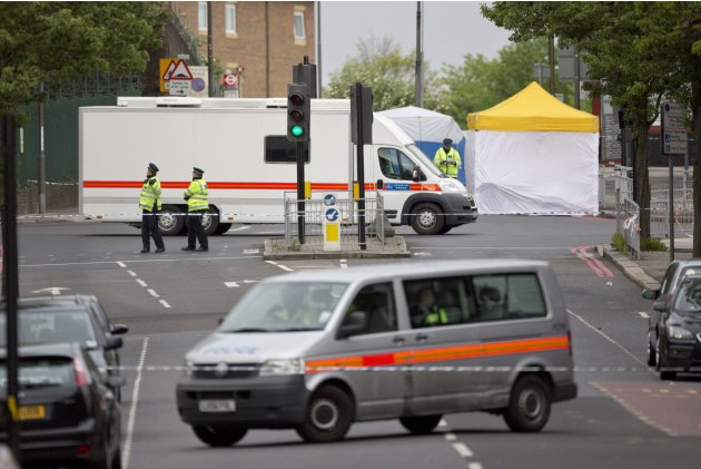 Police officers stand near the scene where a British soldier was killed in Woolwich, southeast London