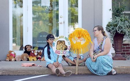 A family sits in front of the doorway of Bloomington's River Bluff Dental clinic in protest against the killing of a famous lion in Zimbabwe