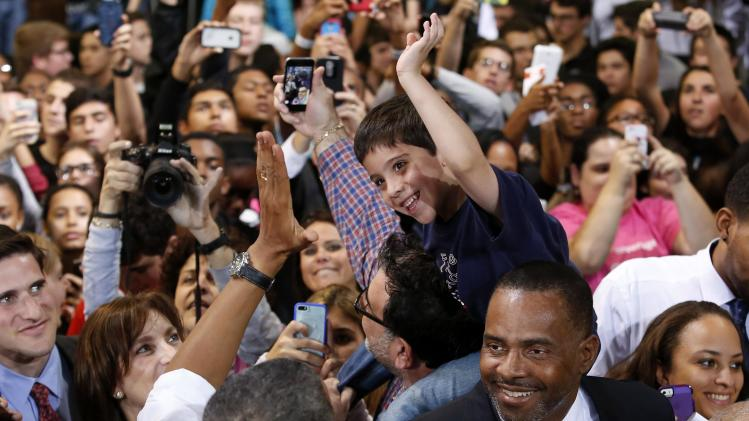 A boy reaches to give a high-five to U.S. President Barack Obama at the Coral Reef High School in Miami