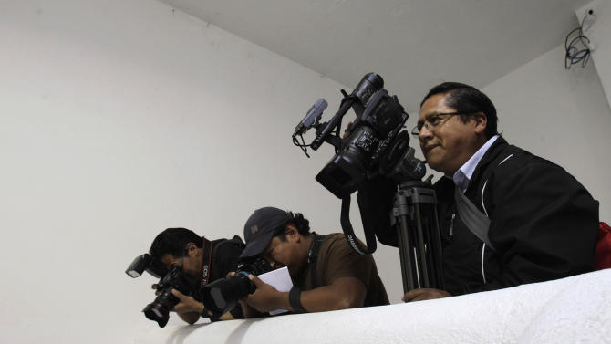 In this Aug. 31, 2012 photo, photographers cover the National Electoral Council in Quito, Ecuador. To Ecuador's President Rafael Correa, Australian-born Wikileaks founder Julian Assange is a truth-teller who deserves praise and protection as he knocks down the walls of government secrets.  But when it comes to Ecuador's opposition media, Correa says too many journalists serve special interests and have immense, unchecked power.  (AP Photo/Dolores Ochoa)