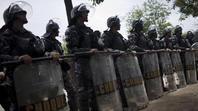 Police in riot gear form a cordon outside an old Indian museum, in preparation for the eviction of  an indigenous settlement of men and women living on the grounds of the old museum, in Rio de Janeiro, Brazil, Saturday, Jan. 12, 2013.  The settlement is next to the Maracana stadium which is being refurbished to host the opening and closing ceremonies of the 2016 Olympics and the final match of the 2014 World Cup. Authorities say the compound must go as the area around the stadium is also being refurbished, expected to be transformed into a shopping and sports entertainment hub. (AP Photo/Felipe Dana)