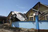 A car rests on the concrete fence of a house Sunday, Dec. 18, 2011 at Iligan city in southern Philippines. Tropical storm Washi blew away Sunday after devastating the southern Philippines with flash floods that killed hundreds of people as they slept and turned two coastal cities into a muddy wasteland filled with overturned cars and uprooted trees. (AP Photo/Bullit Marquez)
