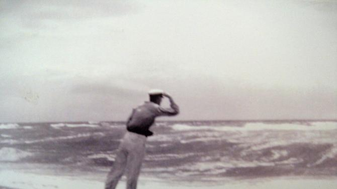 In this 1930s photo provided by the Hendrickson family, Richard Hendrickson leans into the wind as a storm hits a Long Island, N.Y. beach. Hendrickson, who started recording temperatures when Herbert Hoover was in the White House, is being honored as the longest serving volunteer weather data collector for the National Weather Service for his 84 years of collecting information from his farm on eastern Long Island. (AP Photo/Hendrickson Family)