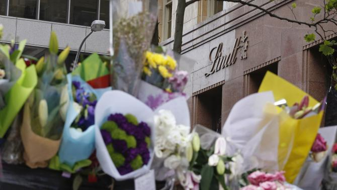 Floral tributes for the victims of Sydney's Lindt cafe siege sit on a fence hear the cafe in Martin Place