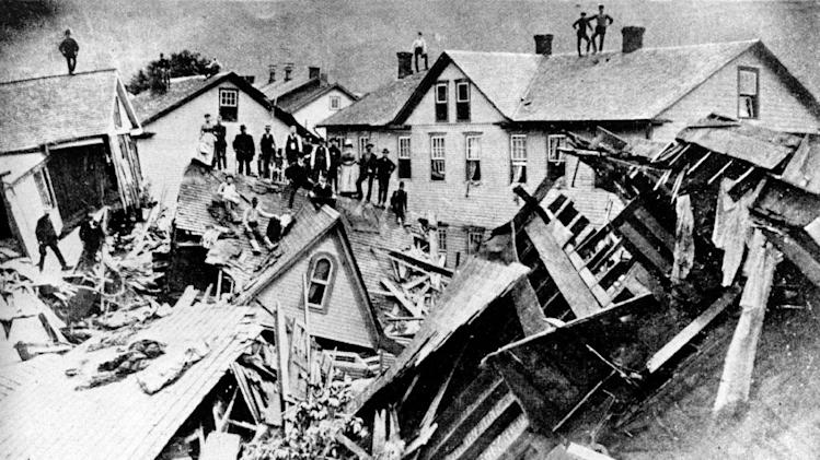 FILE - In this 1889 file photograph, people stand atop houses among ruins after disastrous flooding in Johnstown, Pa. Facts, figures and anecdotes about the Johnstown flood in Pennsylvania, which killed 2,209 people 125 years ago, gave the Red Cross its first international response effort and helped set a precedent for American liability law. (AP Photo/File)
