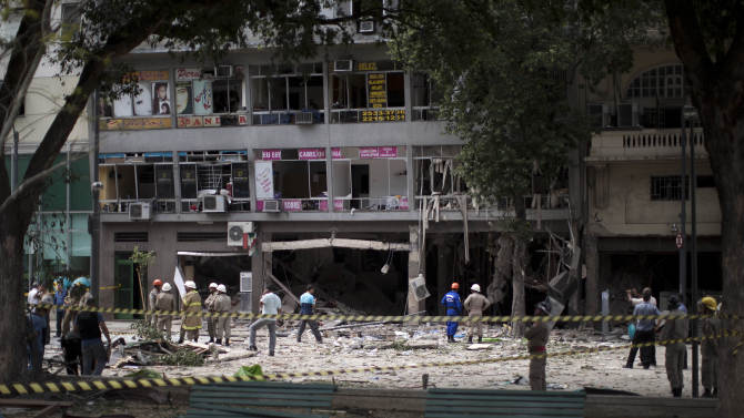 Emergency workers stand among debris after an explosion at a restaurant in Rio de Janeiro, Brazil, Thursday Oct. 13, 2011.  Officials say they are investigating the cause of the explosion that killed at least three people and injured at least 13 others.  (AP Photo/Felipe Dana)