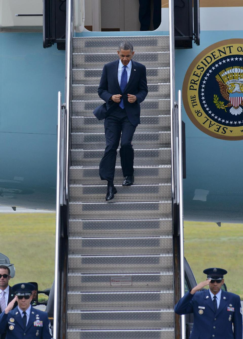 President Barack Obama departs Air Force One at Logan International Airport in Boston, Wednesday, June, 12, 2013, where he was scheduled to attend a fundraiser and rally for Senate candidate, Rep. Ed Markey, D-Mass. (AP Photo/Josh Reynolds)