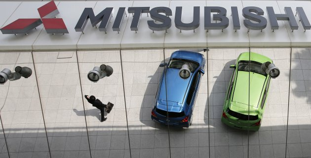 File picture shows Mitsubishi Motors Corp's vehicles reflected on an external wall at the company headquarters in Tokyo