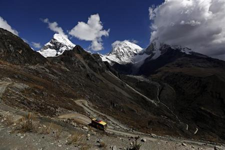 A bus drives on a road in front of Chopicalqui (L) and Huascaran mountains, in Huascaran National Park in Huaraz, September 18, 2013. REUTERS/Mariana Bazo