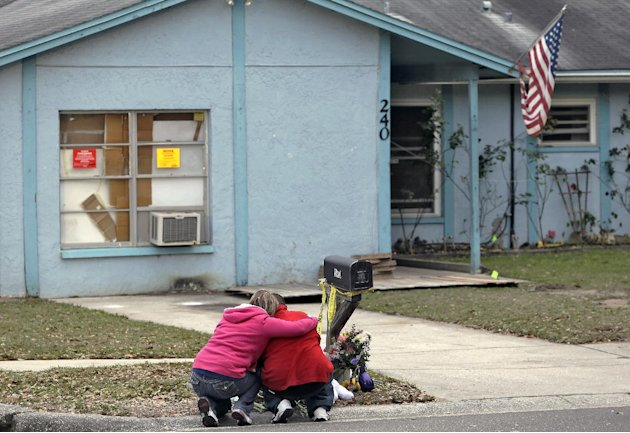 Jeremy Bush, right, is consoled by an unidentified woman Sunday, March 3, 2013, as he sits outside a home where a sinkhole opened up underneath a bedroom late Thursday evening, swallowing his brother,