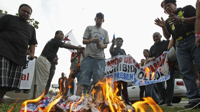 Protesters gather around a burning U.S flag during a march marking the 25th anniversary of the U.S invasion of Panama in Panama City