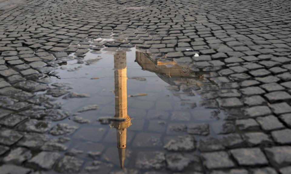 The minaret of the Grand Mosque is reflected in a puddle of water on a cobblestone road in Kosovo's capital Pristina, Sunday, Aug. 19, 2012, marking the first day of Eid al-Fitr celebrations, the end of the holy month of Ramadan. (AP Photo/Visar Kryeziu)