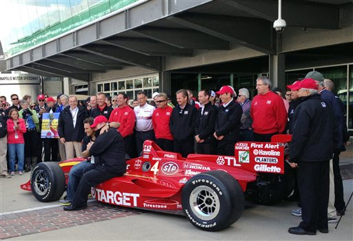 Former CART champion Alex Zanardi, front left, is sits atop a race car with team owner Chip Ganassi at the Indianapolis Motor Speedway in Indianapolis, Friday, May 24, 2013