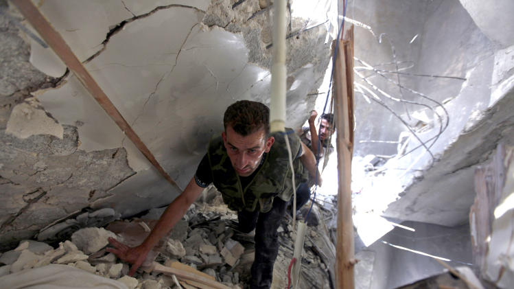 In this Friday Aug. 17, 2012 file photo, Syrian fighters search for survivors under the rubble of a building destroyed in an airstrike by Syrian government planes in Aleppo, Syria. As Syria's rebels gain ground across the country, the fighters are trying to win the hearts and minds of their countrymen and the international community -- capturing army diesel trucks to give to impoverished villagers, working to restore damaged power lines and smuggling in foreign journalists. (AP Photo/Khalil Hamra, File)