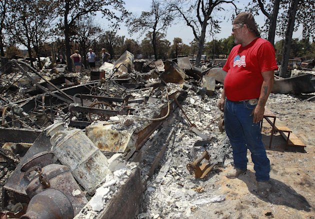 Jim Sparr looks over his wildfire ravaged home near Mannford, Okla, Monday, Aug. 6, 2012. (AP Photo/Sue Ogrocki)