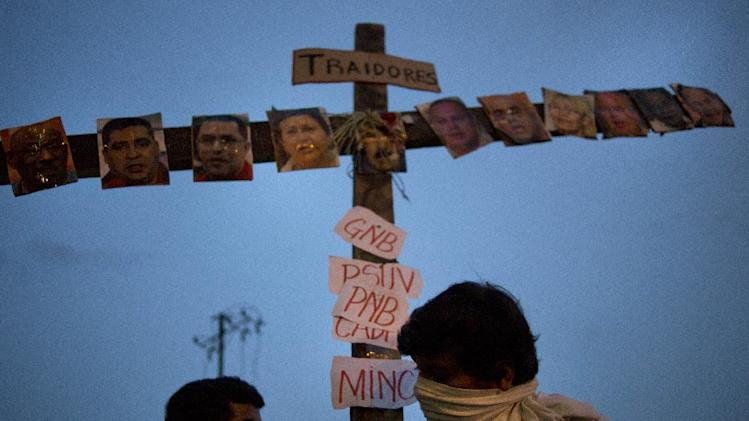 """Anti-government protesters carry a cross covered with photos of government officials and supporters under the Spanish word """"Traitors"""" at a demonstration during Holy Week in Caracas, Venezuela, Wednesday, April 16, 2014. The opposition wants President Nicolas Maduro's government to free jailed opponents and create an independent truth commission to determine responsibility for deaths tied to protests that have rocked the nation since February. (AP Photo/Ramon Espinosa)"""