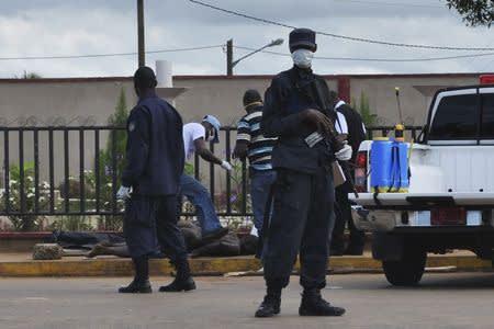 Police stand guard as officers test the body of a man for the Ebola virus, which according to police is standard protocol when bodies are discovered, in Monrovia