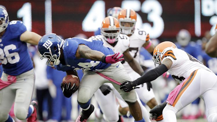 New York Giants running back Ahmad Bradshaw (44) breaks a tackle by Cleveland Browns strong safety T.J. Ward (43) during the first half of an NFL football game Sunday, Oct. 7, 2012, in East Rutherford, N.J. (AP Photo/Kathy Willens)