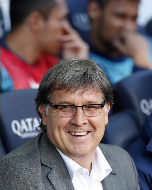"Barcelona's coach Gerardo ""Tata"" Martino smiles as Neymar and Adriano Correia speak on the bench before their Spanish first division soccer match against Osasuna at Camp Nou stadium in B"