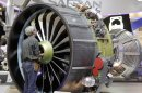 A mechanic works on a Leap jet engine, a CFM International, powering the Airbus A320 neo, during the 50th Paris Air Show at Le Bourget airport, north of Paris, Wednesday June 19, 2013. (AP Photo/Remy de la Mauviniere)