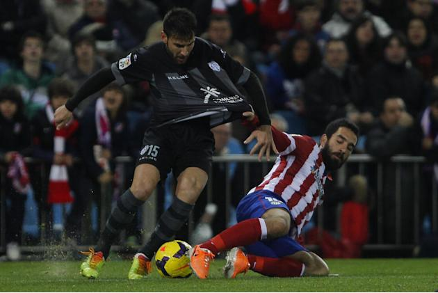 Atletico's Arda Turan from Turkey, right, competes with Nikos Karampelas from Greece, left, during a Spanish La Liga soccer match between Atletico de Madrid and Levante at the Vicente Calderon sta