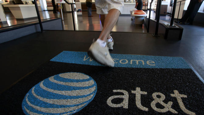 FILE - In this Wednesday, July 20, 2011, file photo, a customer enters an AT&T store in Santa Monica, Calif. AT&T reports quarterly earnings on Tuesday, July 23, 2013. (AP Photo/Reed Saxon, File)
