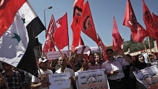 """Palestinians supporters of the Popular Front for the Liberation of Palestine (PFLP), wave their red banners and Syrian flags while chanting anti-American slogans during a protest against a possible military attack by the United States on Syria, in front of the United Nations Special Coordinator for the Middle East Peace Process offices in Gaza City, Tuesday, Sept. 10, 2013. President Barack Obama has been seeking international and congressional support for limited strikes against Assad's government, in response to accusations of chemical weapons use by Syria in an Aug. 21 assault near the capital Damascus. Arabic on banners reads """"the aggression on Syria is a violation of international law"""" and """"we call on the free nations and free people on the world to voice their anger and demands to stop the planned aggression on Syria."""" (AP Photo/Adel Hana)"""