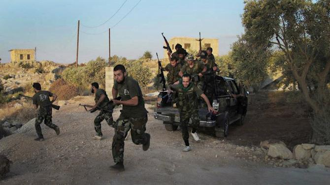 In this citizen journalism image taken on Friday, July 13, 2012 and provided by Edlib News Network ENN, Free Syrian Army soldiers run for cover in Idlib province, northern Syria. (AP Photo/Edlib News Network ENN) THE ASSOCIATED PRESS IS UNABLE TO INDEPENDENTLY VERIFY THE AUTHENTICITY, CONTENT, LOCATION OR DATE OF THIS HANDOUT PHOTO