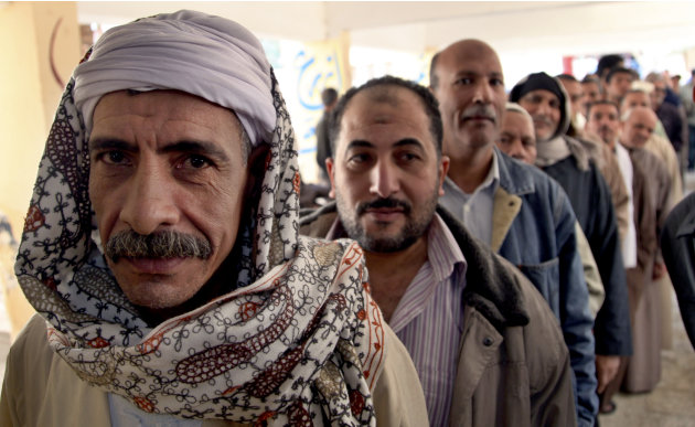 Egyptian men line up outside a polling station to cast their votes during a referendum on a disputed constitution drafted by Islamist supporters of President Morsi in Cairo, Egypt, Saturday, Dec. 15, 