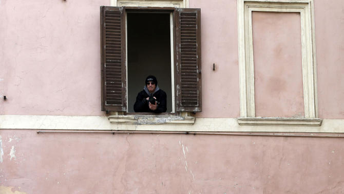 """People peer out of windows of a building facing the papal summer residence in Castelgandolfo, in the outskirts of Rome, Saturday, March 23, 2013. Pope Francis has traveled to Castel Gandolfo to have lunch with his predecessor Benedict XVI in a historic and potentially problematic melding of the papacies that has never before confronted the Catholic Church. The Vatican said the two popes embraced on the helipad. In the chapel where they prayed together, Benedict offered Francis the traditional kneeler used by the pope. Francis refused to take it alone, saying """"We're brothers,"""" and the two prayed together on the same one. (AP Photo/Gregorio Borgia)"""