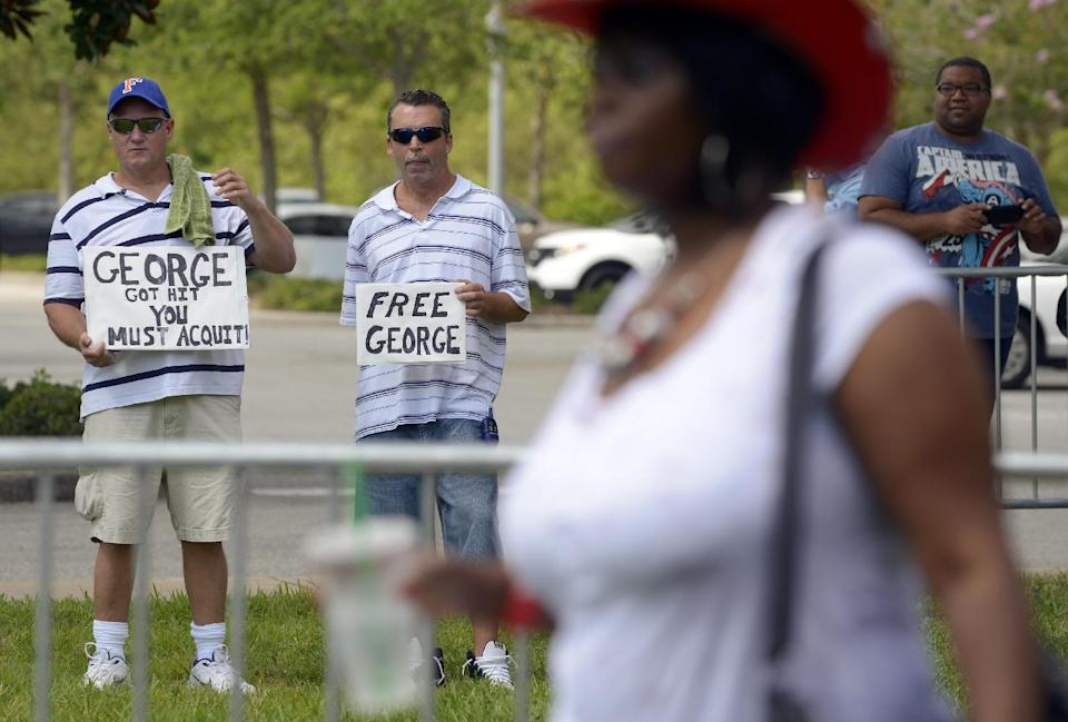 Patrick Woodburn, left, and William Memola hold signs supporting George Zimmerman in front of the Seminole County Courthouse, Saturday, July 13, 2013, in Sanford, Fla. Zimmerman has been charged in the 2012 shooting death of Trayvon Martin. (AP Photo/Phelan M. Ebenhack)