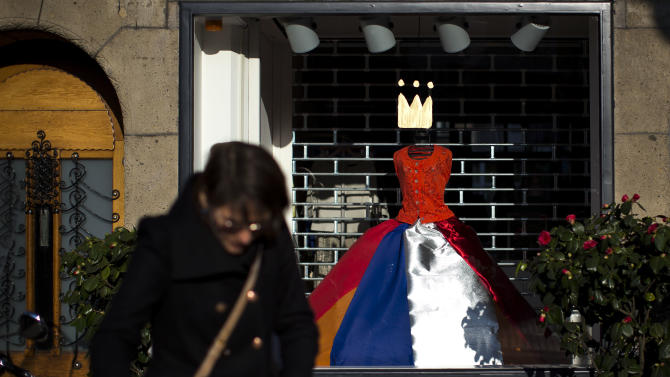 A crown and a dress with The Netherlands flag colors decorates a shop window in Amsterdam, Netherlands Sunday, April 28, 2013. Queen Beatrix announced she will relinquish the crown on April 30, 2013, after 33-years of reign, leaving the monarchy to her son Crown Prince Willem Alexander. (AP Photo/Daniel Ochoa de Olza)