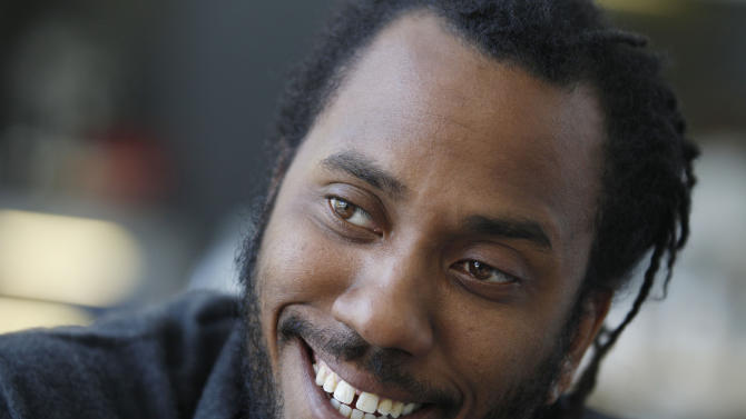 In this photo taken, Friday, April 6, 2012, artist Rashid Johnson smiles during an interview before his first solo exhibition at the Museum of Contemporary Art in Chicago. In the last year, the Chicago native whose works made from everyday objects explore his own life story as well as larger issues of black identity, has garnered high-profile attention and awards from the art world. (AP Photo/M. Spencer Green)
