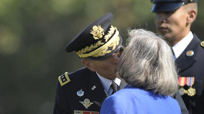 FILE - In this Aug. 31, 2011 file photo, former Commander of International Security Assistance Force and U.S. Forces-Afghanistan Gen. Davis Petraeus kisses his wife Holly during an armed forces farewell tribute and retirement ceremony at Joint Base Myer-Henderson Hall in Arlington, Va. Gen. Petraeus, the retired four-star general who led the U.S. military campaigns in Iraq and Afghanistan, resigned Friday, Nov. 9, 2012 as director of the CIA after admitting he had an extramarital affair. (AP Photo/Susan Walsh, File)