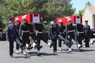 Turkish soldiers carry the coffins of two pilots of a fighter jet shot down by Syria last month. Turkish leaders observed a minute's silence Friday in tribute to the two-man crew of the warplane