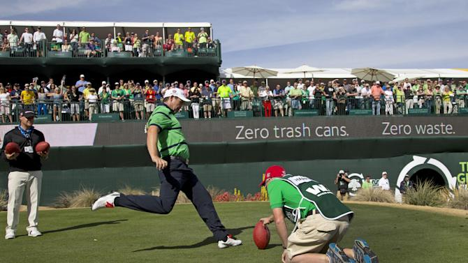 Padraig Harrington, of Ireland, kicks an official NFL Super Bowl XLVII football towards the gallery as caddie Ronan Flood holds on the 16th green during the third round of the Phoenix Open golf tournament, Saturday, Feb. 2, 2013, in Scottsdale, Ariz. (AP Photo/The Arizona Republic, Rob Schumacher) MESA OUT  MARICOPA COUNTY OUT  MAGS OUT  NO SALES