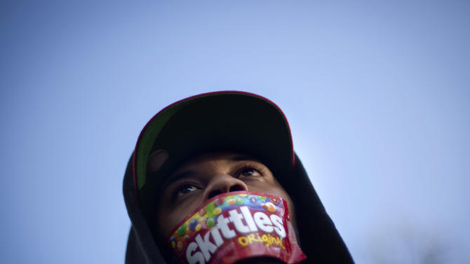 "FILE - In this March 26, 2012 file photo, Jajuan Kelley, of Atlanta, wears a Skittles wrapper over his mouth during a rally in memory of Trayvon Martin, the unarmed 17-year-old who was killed by a Florida neighborhood watch captain while returning from a convenience store with a bag of Skittles and an iced tea, in Atlanta. Skittles isn't the first popular food brand to find itself at the center of a major controversy. The terms ""the Twinkie defense"" and ""don't drink the Kool-Aid"" became part of the vernacular decades ago in the wake of tragic events. More recently, Doritos made headlines when it was reported that the corn chips were Saddam Hussein's favorite snack. (AP Photo/David Goldman, File)"