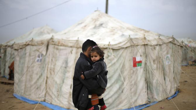Palestinian man carries sister near tents erected by Palestinians whose houses were destroyed by what witnesses said was Israel shelling during 50-day conflict last summer, east of Khan Younis in Gaza