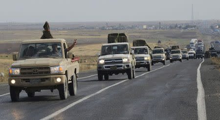 A convoy of peshmerga vehicles makes its way to the Turkish-Syrian border, near the town of Kiziltepe, in the southeastern Mardin province