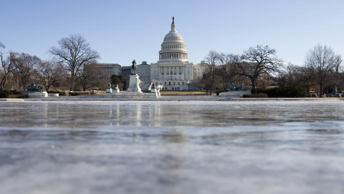 The reflecting pool in front of the U.S. Capitol building is frozen over, Tuesday, Jan. 7, 2014 in Washington. Frigid air that snapped decades-old records will make venturing outside dangerous for a second straight day Tuesday, this time spreading to southern and eastern parts of the U.S. and keeping many schools and businesses shuttered. Residents driven from their homes by power outages in the Midwest longed to return to their own beds. (AP Photo/ Evan Vucci)