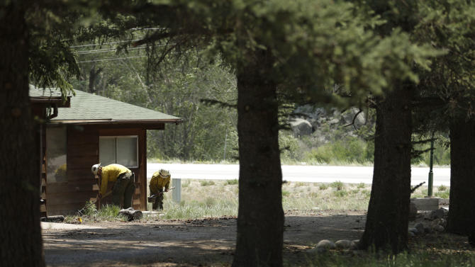 Firefighters from the San Juan Hotshots based in Durango, Colo, clear brush from around structures Saturday, June 22, 2013, in South Fork, Colo. Fire crews with tankers and hoses at the ready stood guard Friday night as a massive and fast-burning wildfire threatened a popular mountain tourist enclave in southwestern Colorado, forcing the evacuation of more than 400 people. (AP Photo/Gregory Bull)