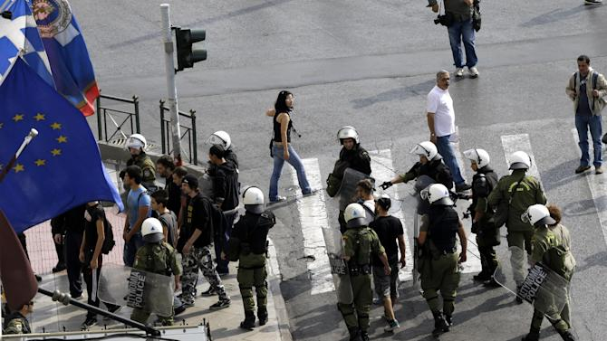 Civilians are detained as precaution by riot police prior to an protest in Athens on Tuesday Oct. 9, 2012. German Chancellor Angela Merkel makes her first visit to Greece since the eurozone crisis began here three years ago. Her five-hour stop is seen by the government as a historic boost for the country's future in Europe's shared currency, but by protesters as a harbinger of more austerity and hardship. More than 7,000 police will be on hand, cordoning off parks and other sections of central Athens, to keep demonstrators away from the German leader who is due to arrive Tuesday in the Greek capital for talks with conservative Prime Minister Antonis Samaras. (AP Photo/Dimitri Messinis)