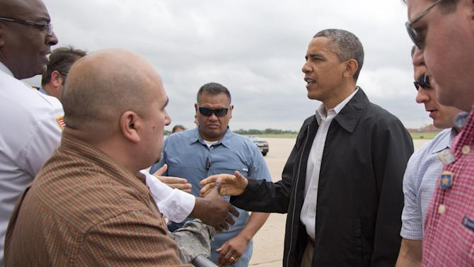 President Barack Obama greets people on the tarmac as he arrives Sunday, May 26, 2013, at Tinker Air Force Base in Midwest City, Okla., en route to the Moore, Okla., to see the response to the severe tornadoes and weather that devastated the area. He will also visit with the families affected, and first responders. (AP Photo/Carolyn Kaster)