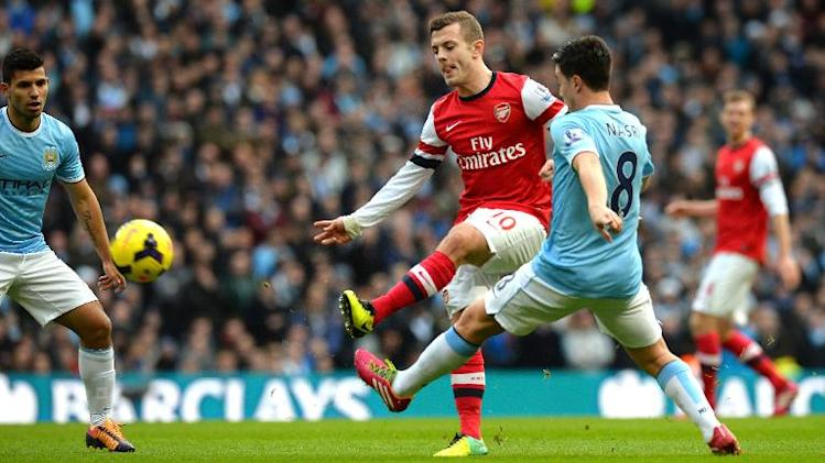 Arsenal's English midfielder Jack Wilshere (C) shoots towards goal during the English Premier League football match between Manchester City and Arsenal at the Etihad Stadium in Manchester on December 14, 2013